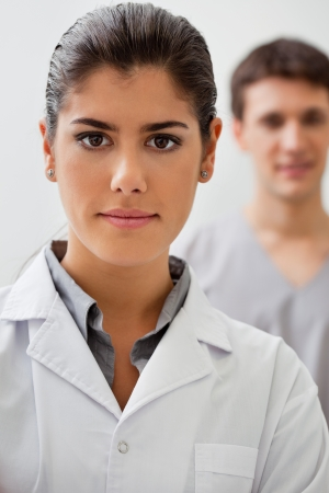 Portrait of confident female doctor with practitioner standing in background photo