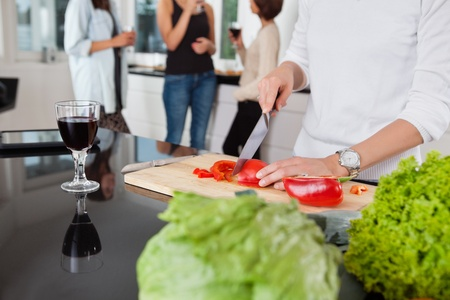 cropped image: Cropped image of female cutting vegetables while friends having drink in background