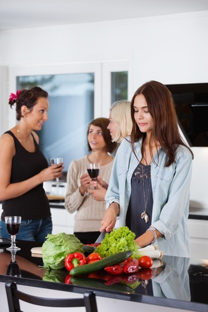 Pretty female cutting vegetables while her friends having drink in background photo