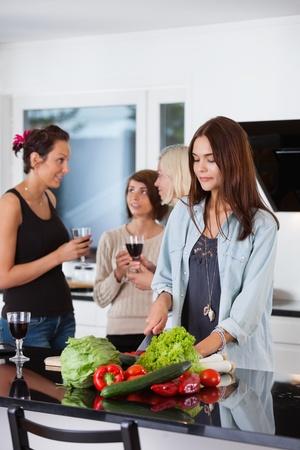 socializando: Pretty femenino cortar verduras, mientras que sus amigos tienen algo en segundo plano