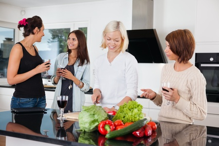 Group of happy female friends in kitchen photo