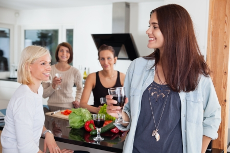 socializing: Group of happy female friends enjoying drink in kitchen