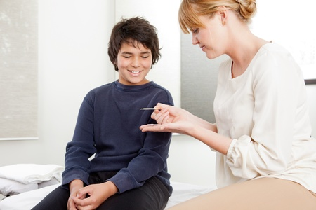 Professional acupuncturist showing needles to young patient photo