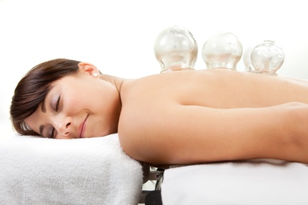 alternative therapies: Female laying on chest with cupping treatment on back