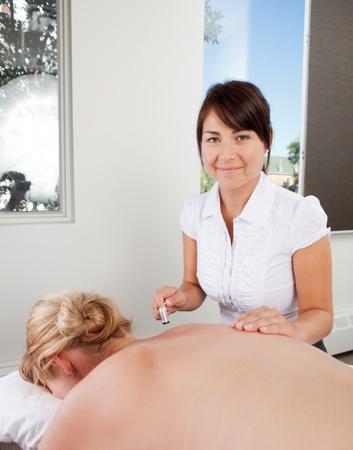 alternative medicine: Portrait of a professional acupuncture therapist holding plumb blossom tool