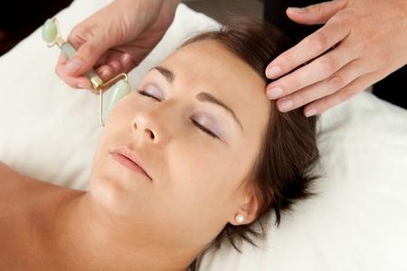 acupuntura china: Atractiva mujer inhalaci�n de masaje facial con rodillos de jade en la acupuntura