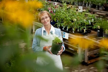 Senior Worker in Garden Center looking at camera photo
