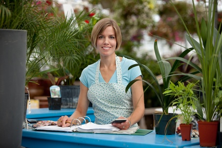 log book: Portrait of a happy greenhouse employee writing in a log book and looking at the camera