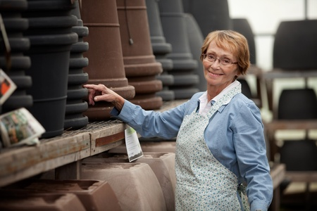 small business owner: Portrait of a senior woman standing by pots in garden center