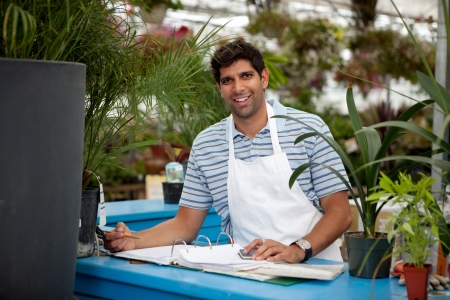 small business owner: Young male garden center employee at check out counter