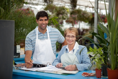 out of business: Young male with senior woman working in a garden center