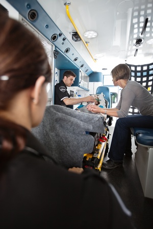 Elderly woman in ambulance being given oxygen, caregiver at side photo