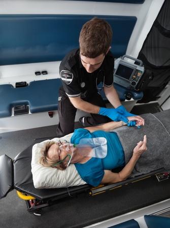 taking pulse: Male ambulance worker taking pulse of elderly senior woman