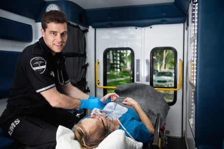 Portrait of a male EMT inside ambulance with senior woman patient photo