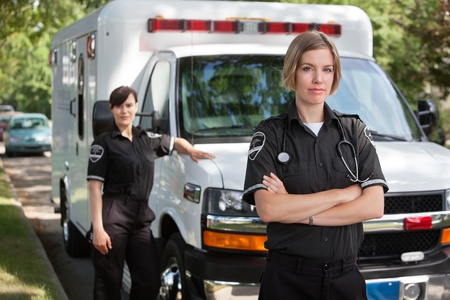 paramedics: Confident emergency medical team portrait standing with ambulance in background