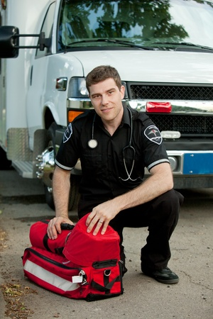 emt: Portrait of a male paramedic in front of ambulance with portable oxygen unit Stock Photo