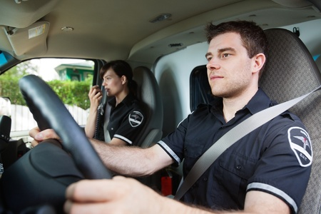 paramedic: Portrait of EMS worker driving ambulance while team member talks with dispatcher
