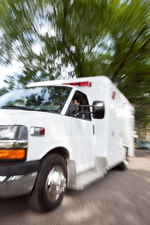 Motion blur of ambulance speeding with female paramedic driving photo
