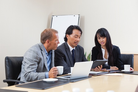 Businesspeople discussing while looking at electronic tablet photo