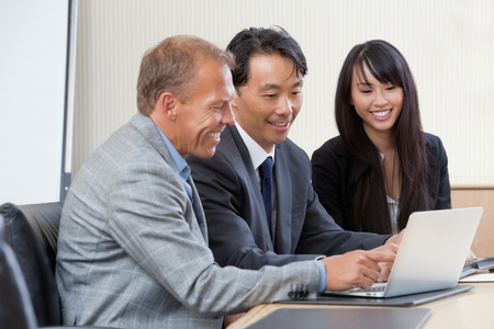 asian business team: Diverse group of businesspeople working on laptop