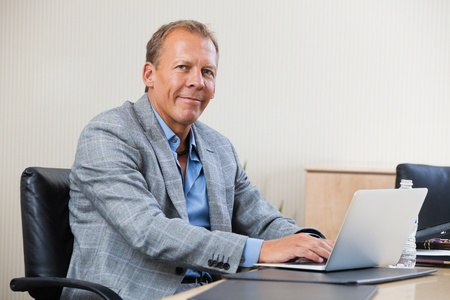 Portrait of smiling businessman working on laptop photo