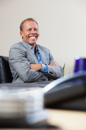 Portrait of smiling mature executive sitting with hands folded photo