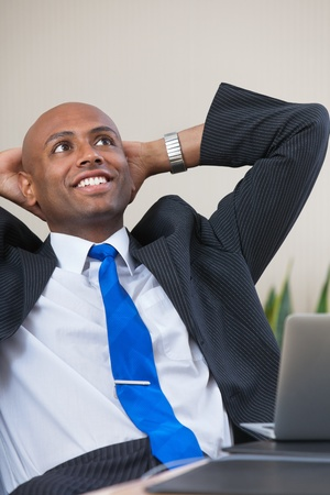 Relaxed Afro American business man sitting at his desk looking into the air photo