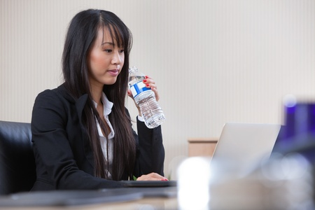 Young beautiful businesswoman drinking water at work photo