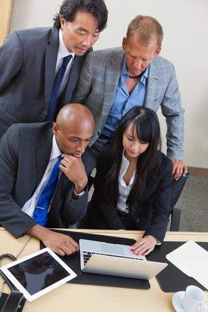 ラップトップ コンピューターで作業一緒に深刻なビジネス チームの肖像画 写真素材
