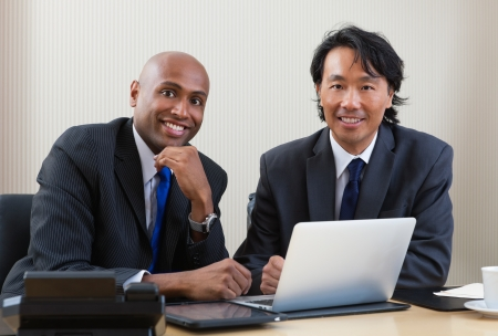 Portrait of multi ethnic business people working on laptop and digital tablet Stock Photo - 11173384