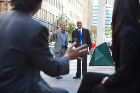 Business people waving and greeting friends on street photo