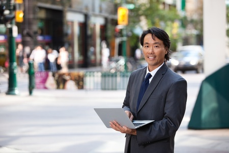 Portrait of handsome businessman using laptop and smiling photo
