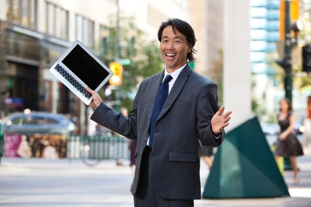 Portrait of successful businessman holding laptop and laughing photo