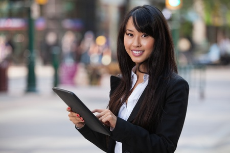 Portrait of smiling business woman using tablet pc photo
