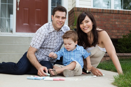 Portrait of happy family playing outside house on sidewalk photo