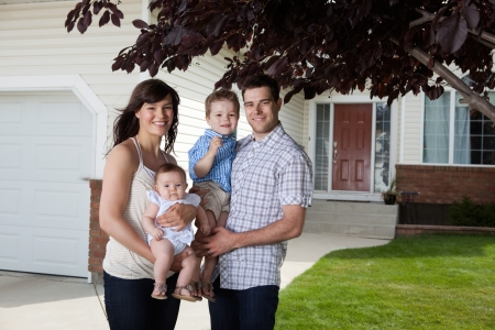Portrait of sweet family standing in front of their house photo