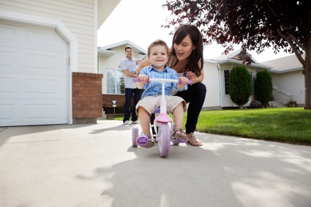 tricycle: Beautiful happy young mother teaching her son to ride bike Stock Photo