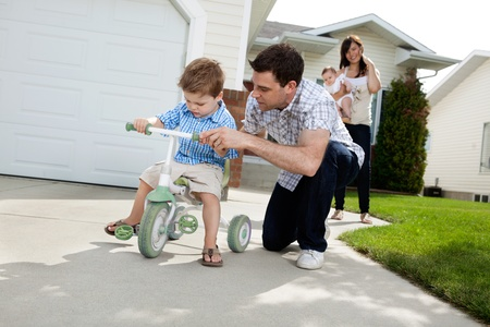 tricycle: Father teaching his son to ride tricycle while wife standing in background Stock Photo