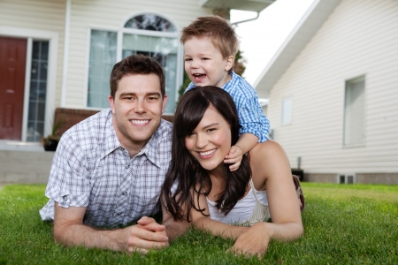 Portrait of cheerful family lying down on grass in front of house photo