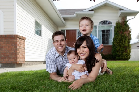 family on grass: Portrait of happy family lying down on grass in front of house Stock Photo
