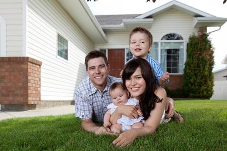 esposas: Retrato de familia feliz acostado en el c�sped frente a la casa Foto de archivo