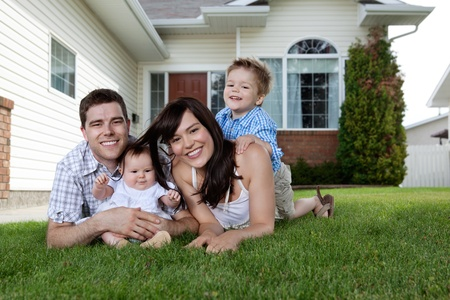 family at home: Happy couple lying down on grass with their adorable children