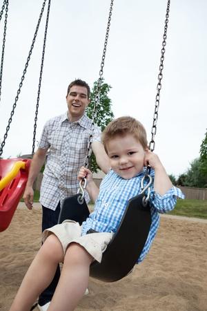 niño empujando: Padre feliz empujando a su hijo en un columpio