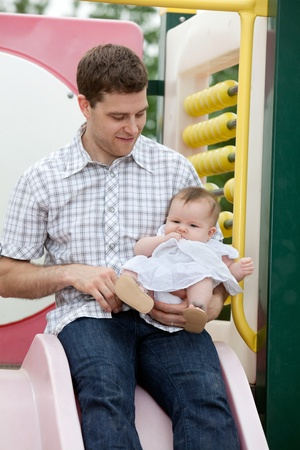 Father sitting on slide with his adorable daughter Stock Photo - 11538779