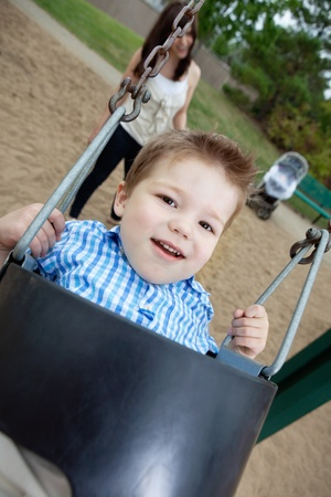 Close-up portrait of small boy swinging while mother standing in background photo