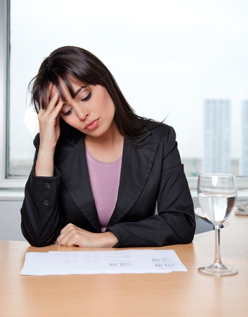 tensed: Beautiful business woman with hand on head at workplace Stock Photo