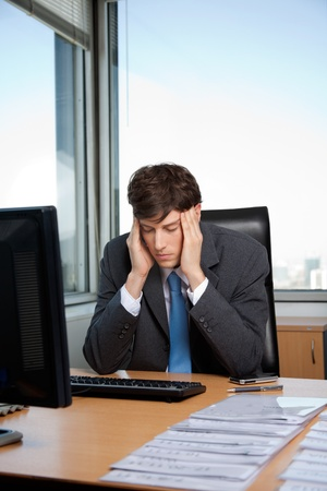 Stressed business manager sitting at his desk Stock Photo - 11538798