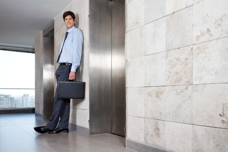 people in elevator: Low angle view of handsome corporate manager standing near lift