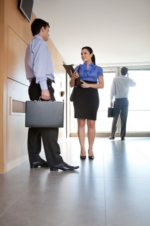 executive assistant: Full length of business people talking in office hallway