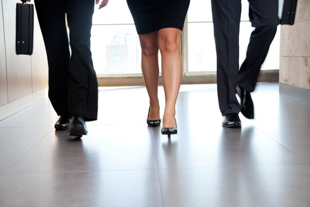 anonymous: Low section of businesspeople walking along the office corridor